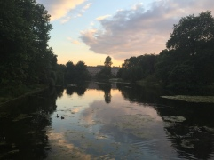 Sun sets over a pond in Saint James park in front of Buckingham Palace