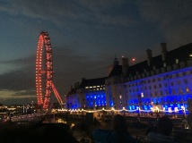 The London Eye, lit in red, sits next to another building lit in blue along the Thames