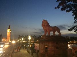 A lion statue sits on one end of a bridge with Big Ben in the background