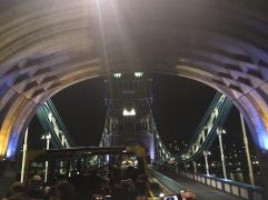 A tour bus passes under a tunnel on the London Bridge