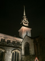 The spire of a church lit from below in sharp contrast to the night sky