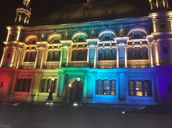 The front of a building in London lit in rainbow colors