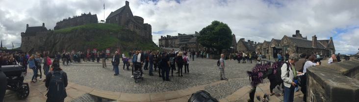 Crowds of people stand in the courtyard viewing different parts of Edinburgh Castle