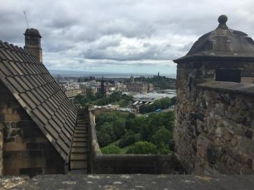 Edinburgh sits in the distance between stone buildings in Edinburgh Castle