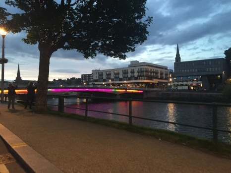 A colorful illuminated bridge spans the river in Inverness at dusk