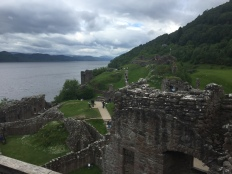 The courtyard and ruined buildings of Urquhart Castle with Loch Ness in the background