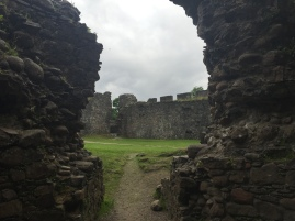 The courtyard of Inverlochy Castle through a crumbling doorway