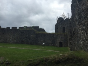 A corner of the courtyard of Inverlochy castle where a tower is surrounded by scaffolding during repairs