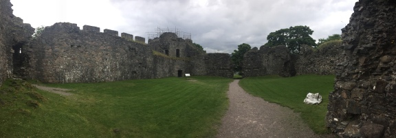 The courtyard of Inverlochy Castle surrounded by crumbling walls and towers