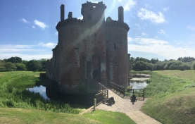 The moat and bridge leading to the gatehouse of Caerlaverock Castle on a sunny day