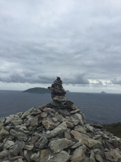 A stone cairn on a small peninsula near the ocean with islands visible in the background