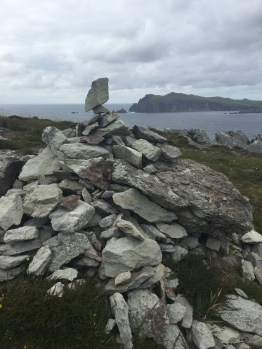 One of many stone cairns with cliffs and the ocean visible in the background