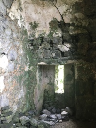 The interior of the ground floor of a crumbling Irish tower house. Fallen stones line the floor and cracks are visible in the wall