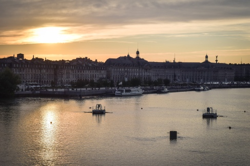 Sun sets over the even and unbroken skyline of Bordeaux from the bridge over the river