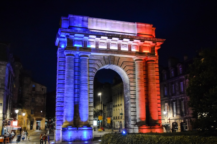 A triumphal arch in Bordeaux lit in blue, white, and red