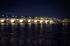 An illuminated bridge with many arches spans the river in Bordeaux at night