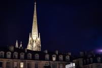 The spire of a cathedral in Bordeau illuminated at night