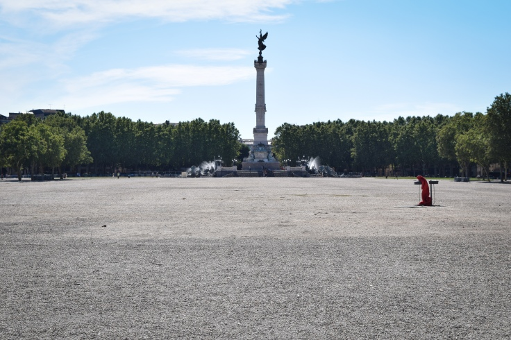 A monument rises in a large empty gravel plaza in Bordeaux