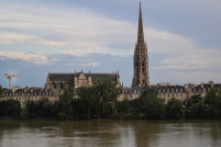 A cathedral and spire in Bordeaux behind the river
