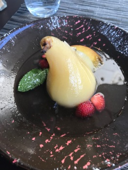 An Anjou pear poached in a white wine sauce with strawberries and mint