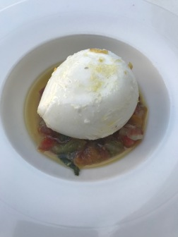 A large ball of mozzarella sits atop diced vegetables and oil in a large white bowl