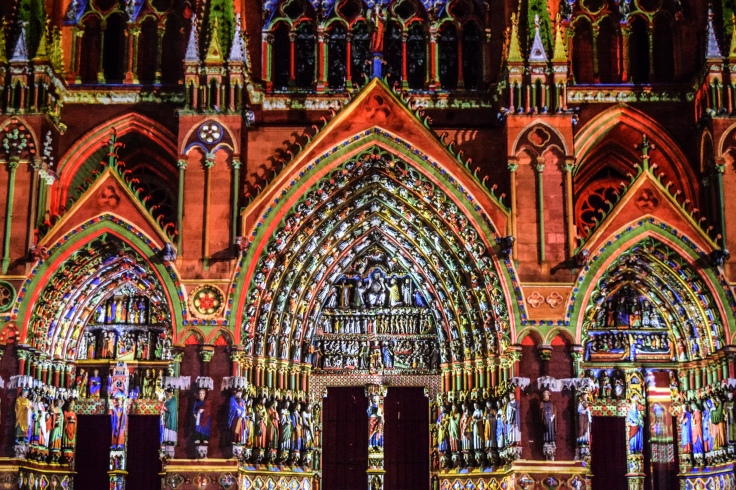 Facade of the Amiens Cathedral lit in bright colors for the nightly light show