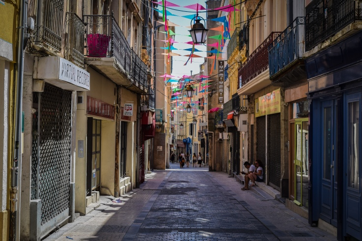 A narrow street lined shop in Narbonne covered with colorful kites