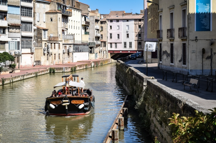 A boat on the Canal de la Robine with the Pont des Marchands in the background