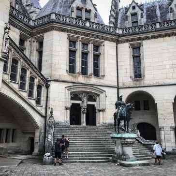 A statue standing in front of the staircase leading into the Chateau de Pierrefonds from the courtyard