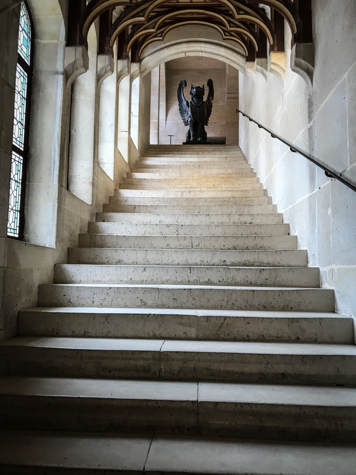 A stairwell inside the Chateau de Pierrefonds leading up to a statue of a griffin.