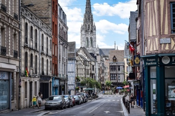 A street in Rouen full of half-timbered houses and the spire of a cathedral