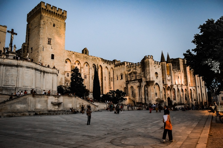 The Palace of the Popes and surrounding plaza filled with street performers in Avignon