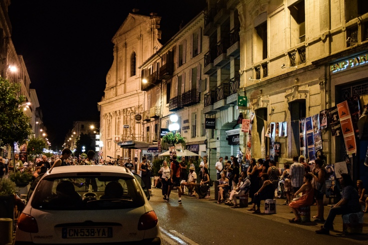 Crowds surround street performers on the busy streets during the Avignon Festival Off
