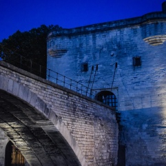A gatehouse stands at the end of the Pont d'Avignon at dusk