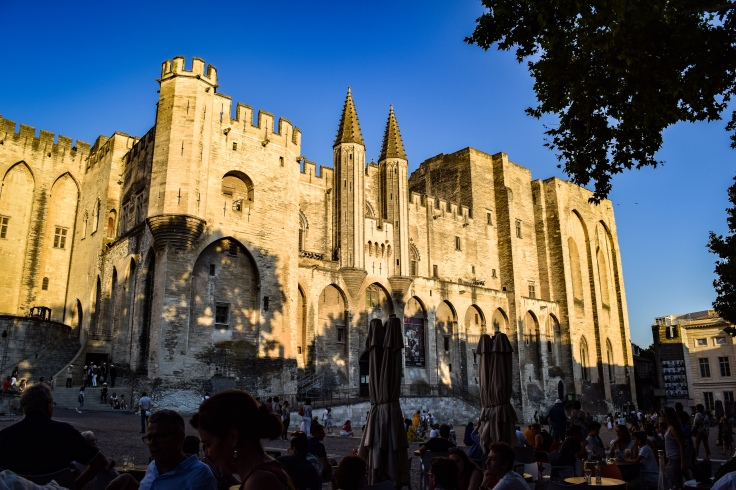 Palais des Papes and the plaza filled with diners and street performers in Avignon