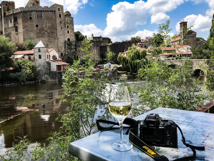 My glass of wine and camera in front of the river, bridge, and castle of Clisson