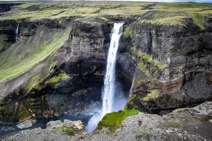 One of the falls in Haifoss tumbling down into the gorge surrounded by mist at the bottom