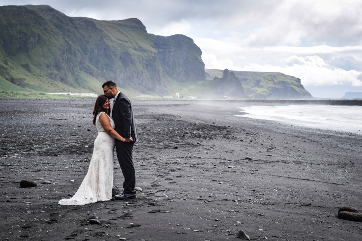 My brother-in-law kissing my sister on the forehead in front of the mountains on a black sand beach