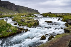 An unnamed waterfall and rapids along a dirt path in Iceland running along some cliffs
