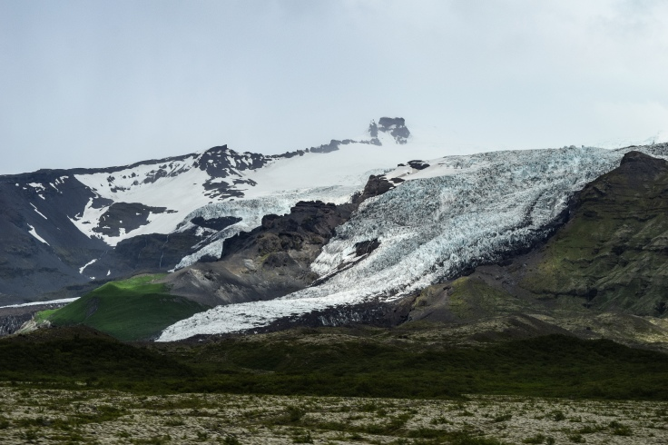 A glacier creeps slowly down the mountainside in Iceland