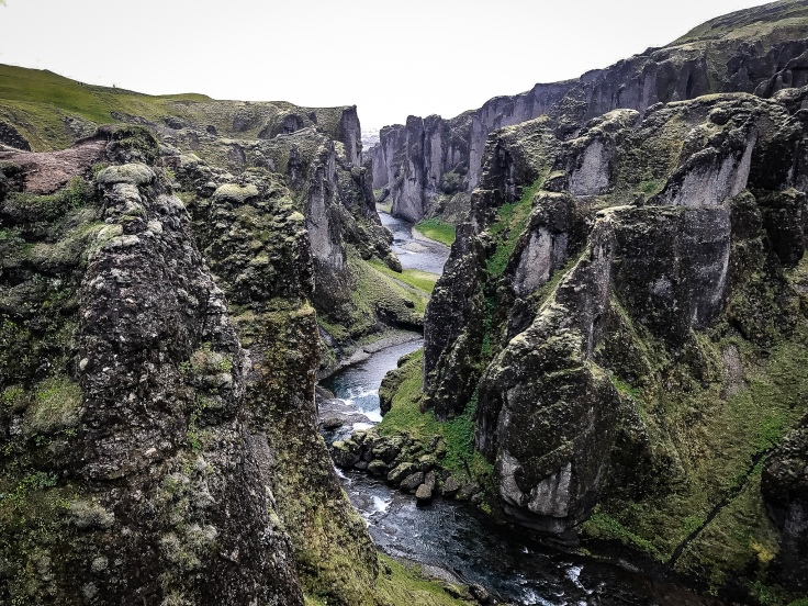 A deep gorge cut by a blue river running out to sea