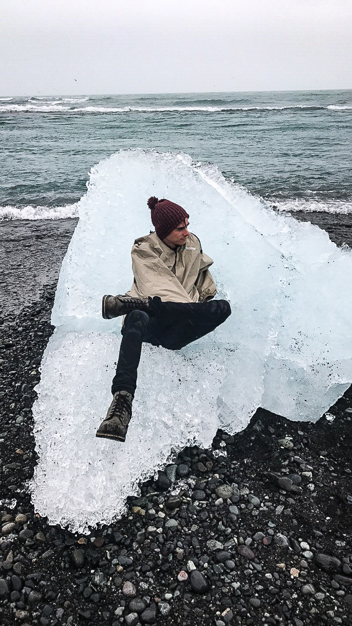 Me dressed in boots and a rain jacket sitting on a large chunk of ice from the glaciers in Iceland