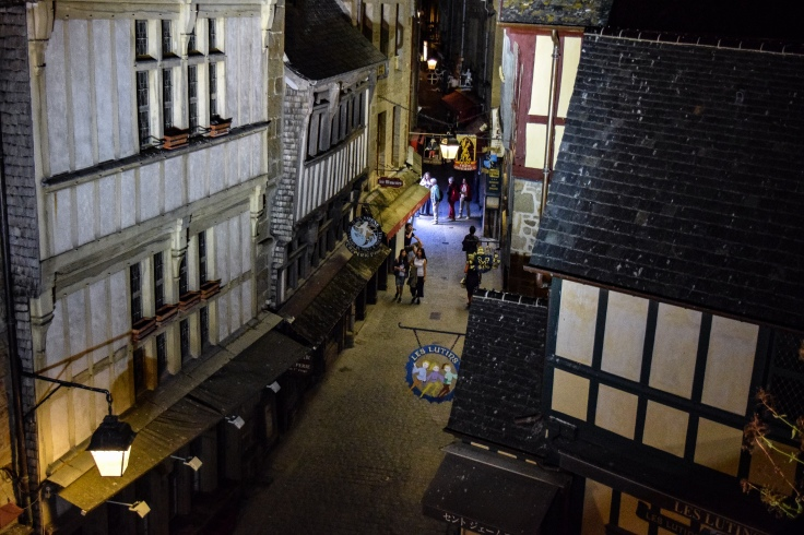 The narrow shop lined streets of Mont Saint Michel at night