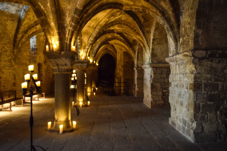 A candlelit vaulted gallery inside Mont Saint Michel