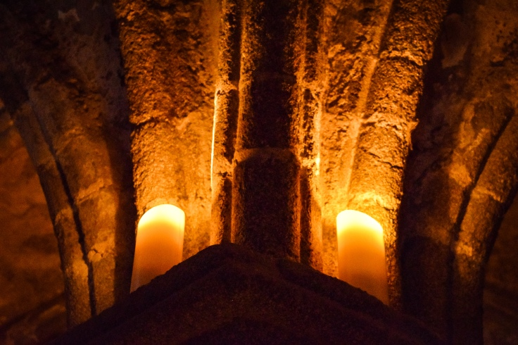 Candles lighting the vaulted ceilings during the nighttime tours of Mont Saint Michel