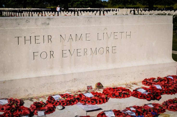 A sign saying their name liveth for evermore in front of rows of tombstones at the Bayeux War Cemetery