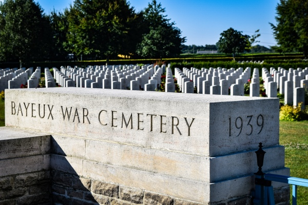 Hundreds of identical white tombstones lie in rows behind the sign for the Bayeux War Cemetery