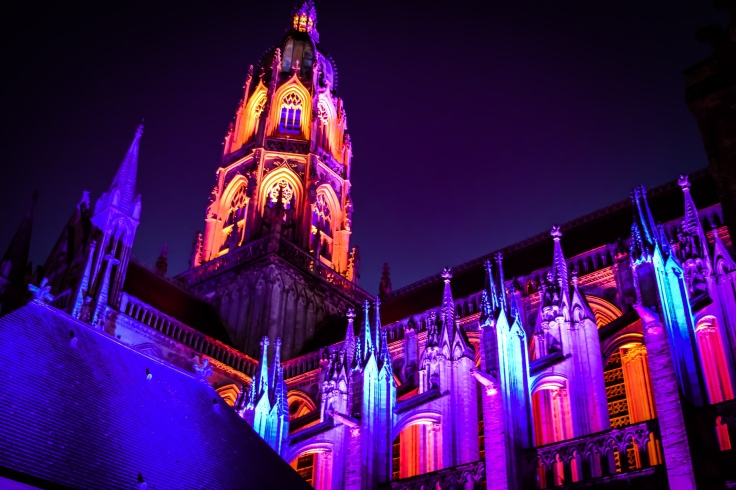 Cathedale de Notre-Dame in Bayeux lit in blue, purple, and orange at night