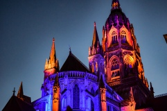 The Bayeux Cathedral lit in orange and purple at dusk