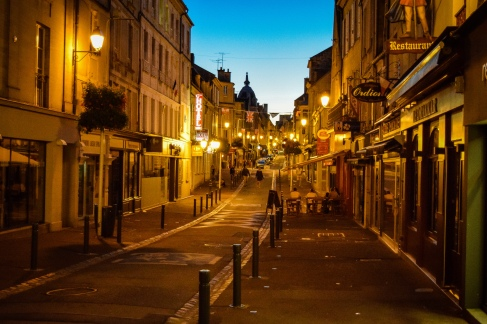 Streetlights and shops line the main pedestrian avenue running through the old town in Bayeux
